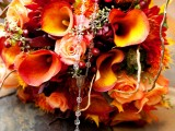 a super colorful fall wedding bouquet of orange and depe red blooms, berries, twigs is a very eye-catchy and bold solution to rock