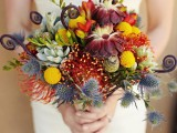 a colorful fall wedding bouquet of burgundy and rust blooms, thistles, billy balls, succulents and lotus is an eye-catchy idea to try