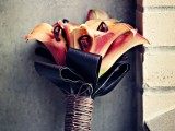 a bold Halloween wedding bouquet of orange callas, lotes and black leaves plus a wrap is a bold and statement-like idea