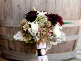 a contrasting fall wedding bouquet of deep purple and white blooms, pale foliage, seed pids and a burlap wrap is a great and non-typical idea for a fall rustic wedding