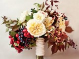 a beautiful fall wedding bouquet of neutral blooms, bold berries, greenery and bright dried leaves is great for a fall wedding