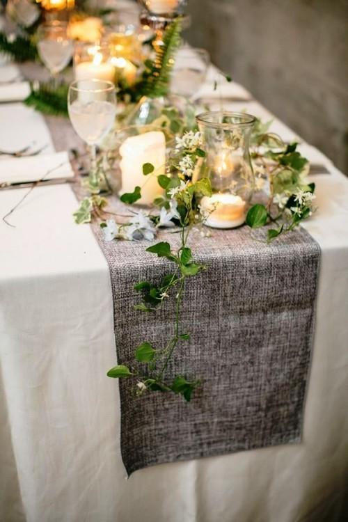 an ethereal greenery table runner combined with a grey fabric table runner and candles for a spring tablescape