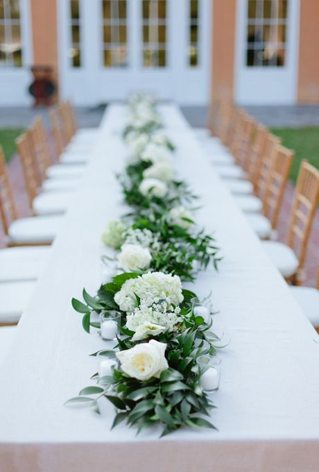 a greenery and white bloom table runner is a stylish idea for a spring wedding or a wedding with a neutral color palette