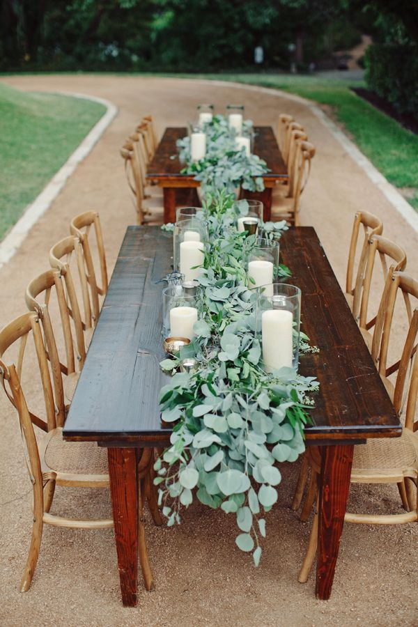 lush eucalyptus table runners and white candles in simple candle holders   and you won't need more for a gorgeous tablescape