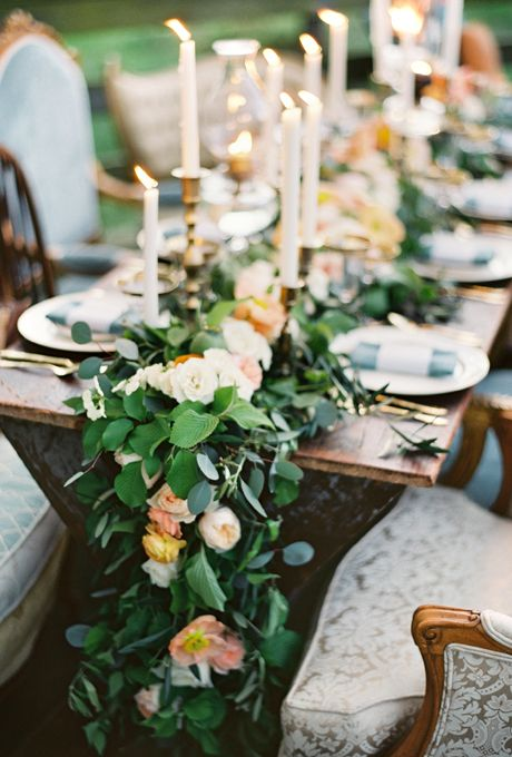 a lush eucalyptus table runner with peachy pink blooms and tall candles is a refined idea to try