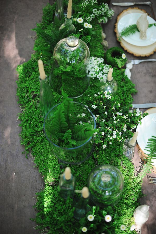 a moss and fern table runner with tiny white blooms and candles is a gorgeous idea for a woodland wedding