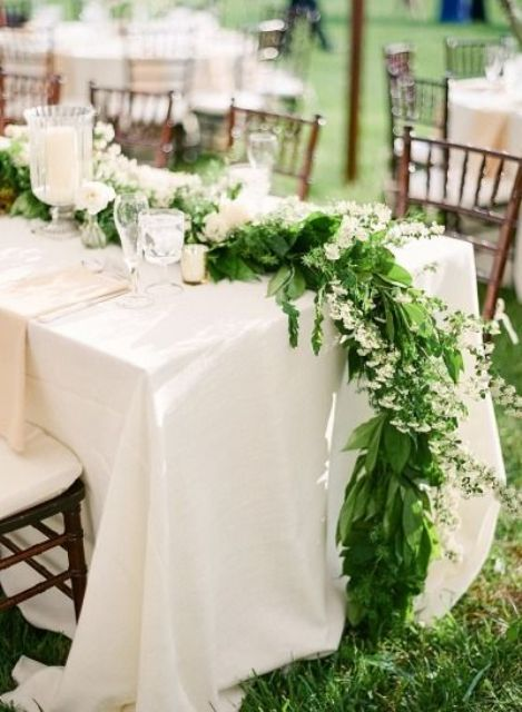 a greenery and white bloom table runner going to the floor, white blooms match white candles