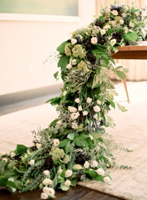 a super lush greenery table runner with white and green blooms looks very chic and textural