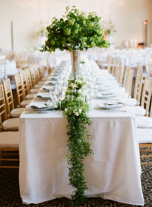 a delicate greenery and white flower table runner and a matching large centerpiece in a vase