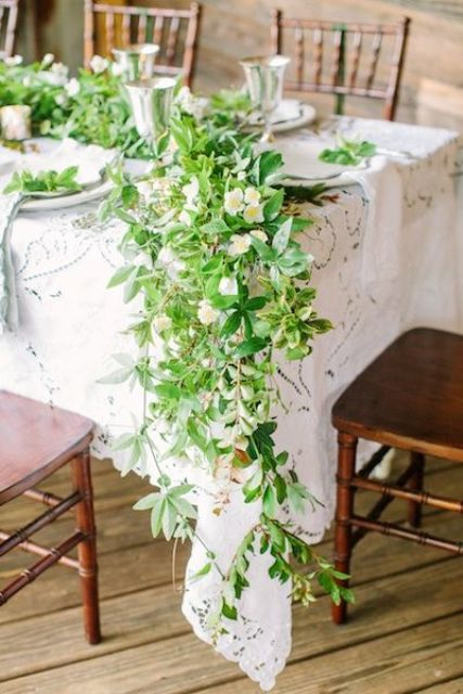 a chic greenery and white bloom table runner that covers half of the table