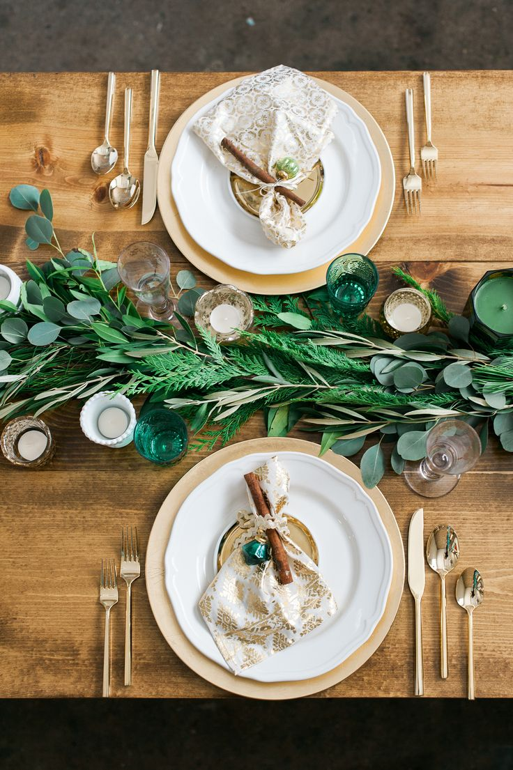 a simple fern and eucalyptus table runner and green and neutral candles for rustic tablescape
