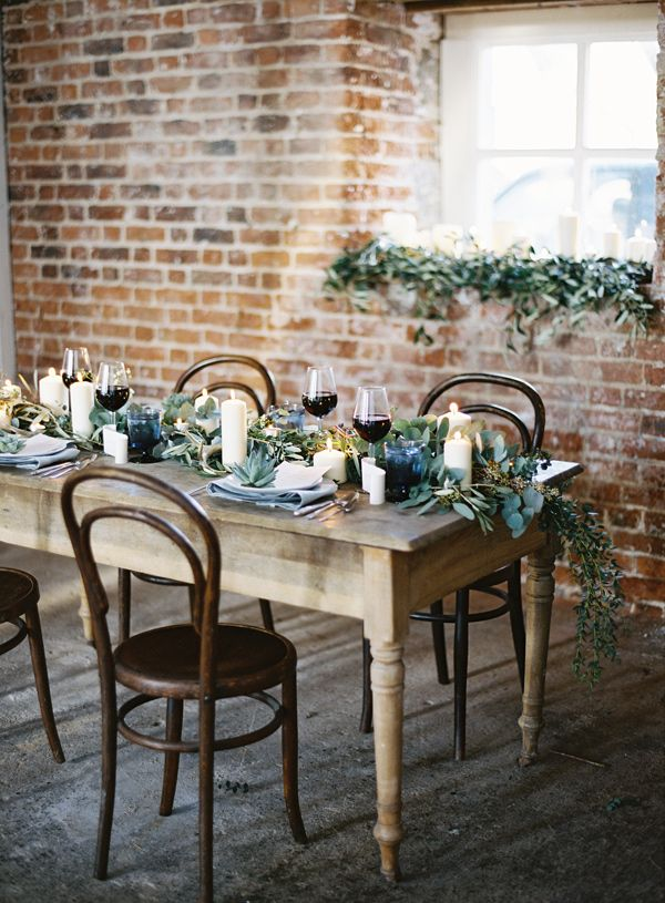 a textural greenery table runner and succulents on each place setting for a stylish look