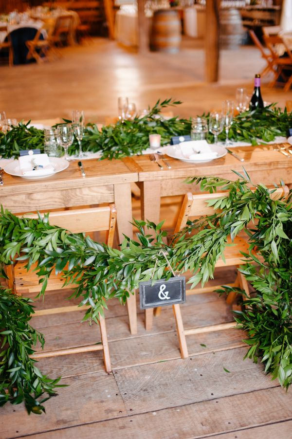 a foliage table runner and a matching garland on the chairs is a chic idea for a rustic space
