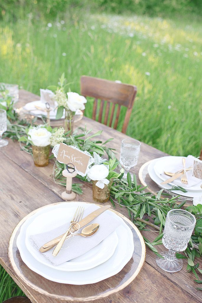 a greenery table runner and white blooms in vases and jars for a cozy rustic table setting
