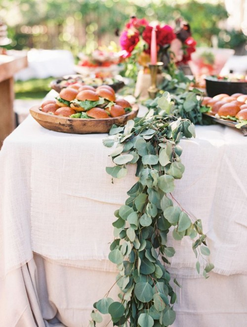 a eucalyptus table runner over a white tablecloth is a chic and timeless idea