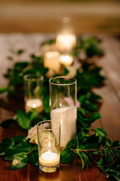 a foliage table runner, white roses, white candles to create an exquisite tablescape