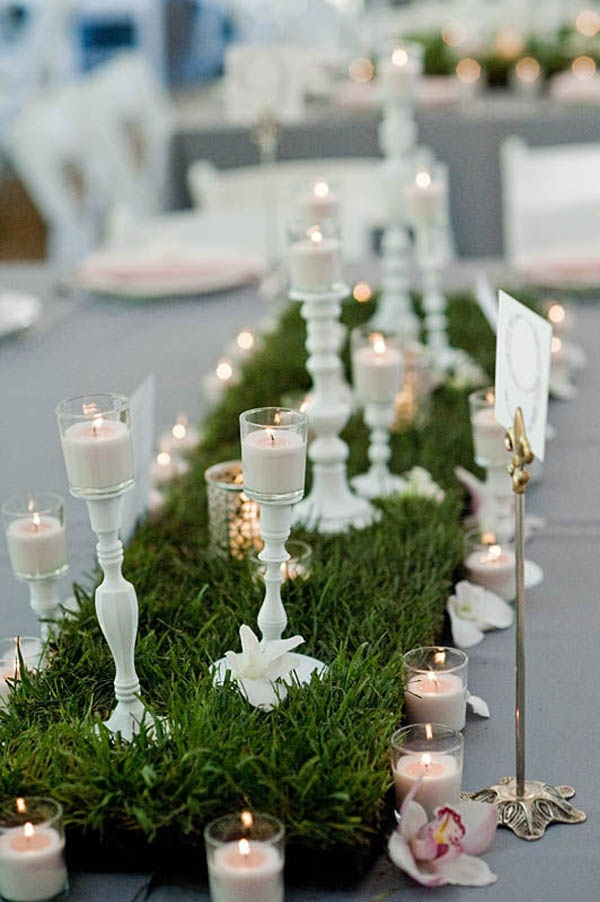 a grass table runner, white candle holders and white candles on top for a vintage feel
