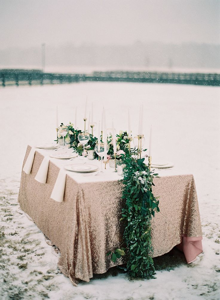 a lush greenery table runner over a copper sequin table runner is a very bold idea