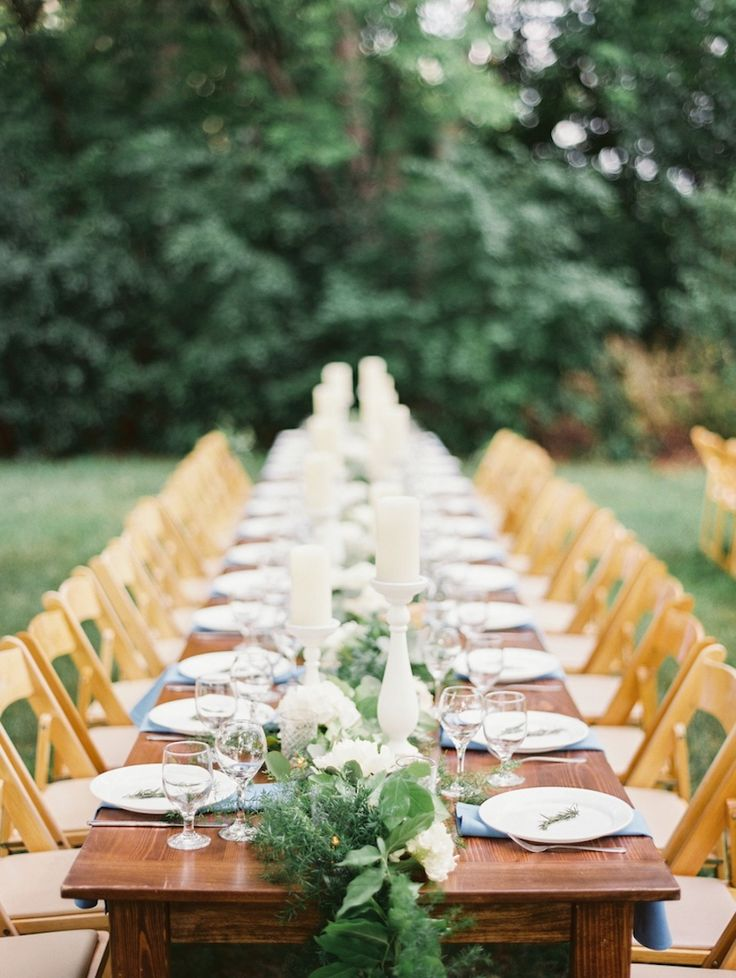 a fern, foliage and white bloom table runner with candles is a chic and bold idea