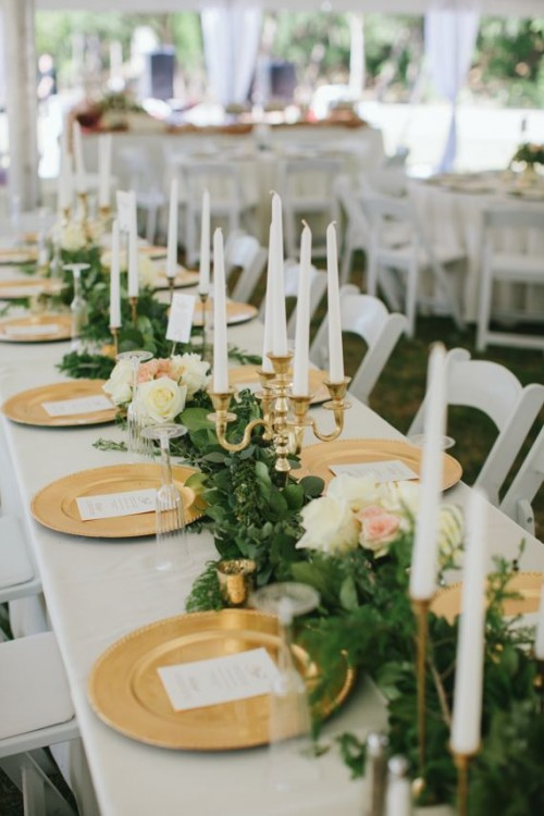 a lush greenery plus white and blush blooms and candles in gilded candle holders for a refined look