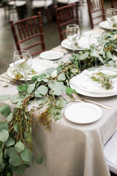 a simple greenery table runner and a grey tablecloth is a cool and very neutral idea