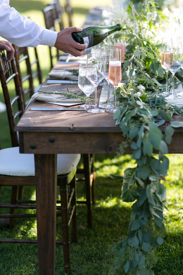 a lush eucalyptus table runner and touches of greenery for each place setting