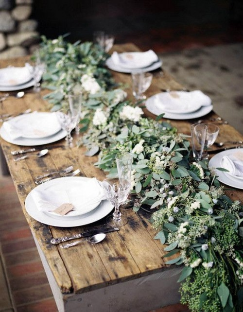a lush and textural greenery table runner with berries is a chic idea for a winter tablescape