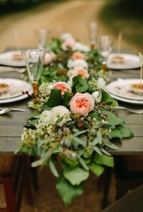 a chic greenery table runner spruced up with neutral and blush blooms on top