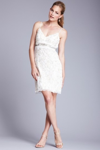 a white lace embellished over the knee dress on spaghetti straps and with an embellished sash for a glam bride