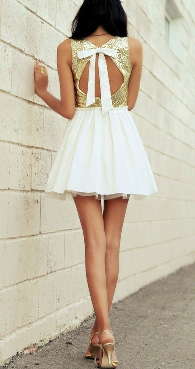 a glam A-line mini dress with a gold sequin bodice, a pleated A-line skirt and a cutout back with a bow