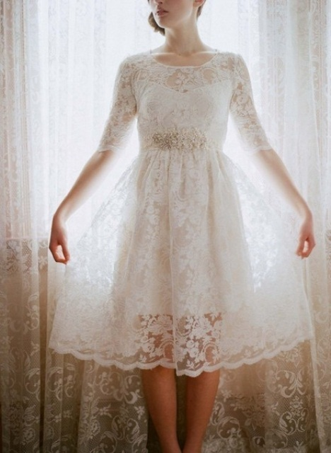 a vintage-inspired white lace A-line knee dress with an illusion neckline, long sleeves and an embellished sash