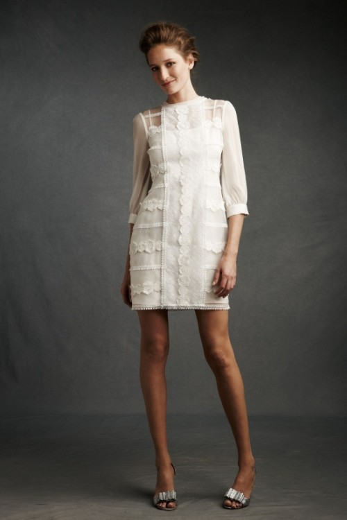 a whimsical white mini dress with short sleeves, an illusion neckline and lace appliques is very chic