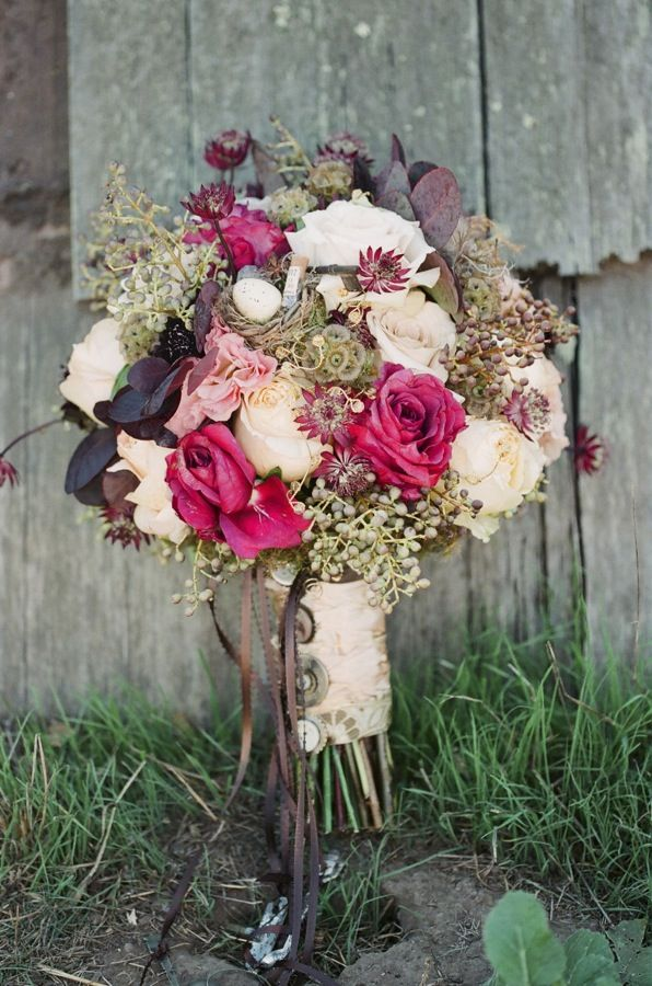 a refined vintage inspired Valentine wedding bouquet with blush, pink blooms and dark leaves plus a vintage wrap with brooches