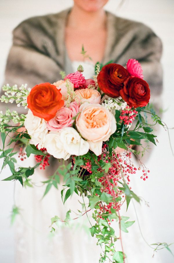 a beautiful Valentine's Day wedding bouquet of blush, peachy, red and burgundy blooms, berries and greenery looks very chic and spectacular