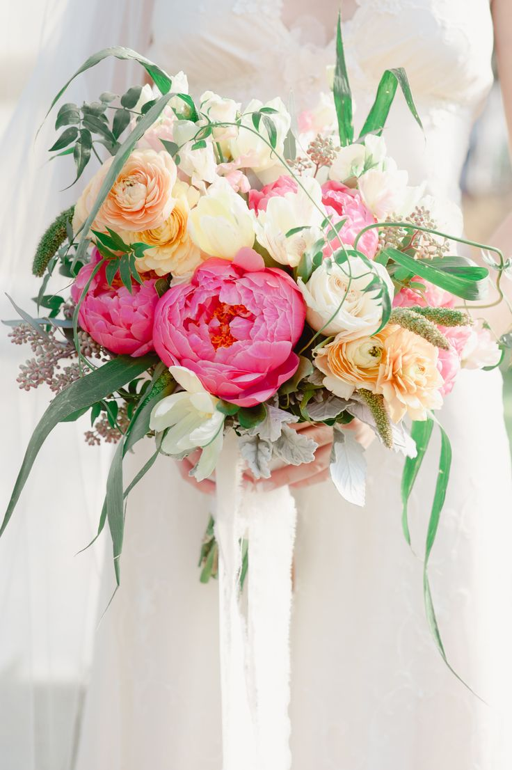 a lovely Valentine wedding bouquet of white, yellow and bold pink blooms and greenery and long white ribbons is beautiful and tender