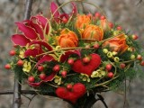 a bold Valentine wedding bouquet of burgundy, yellow blooms, berries, greenery and bold red fabric blooms is a bright idea