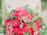 a luxurious wedding bouquet of pink peony roses, lots of greenery and some berries feels and looks like Valentine's Day