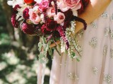 an exquisite blush and deep purple wedding bouquet of roses and peony roses, some greenery looks decadent and very chic