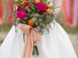 a bright and whimsical wedding bouquet of yellow, fuchsia blooms, messy greenery and some citrus plus a large plaid bow is a statement and real chic