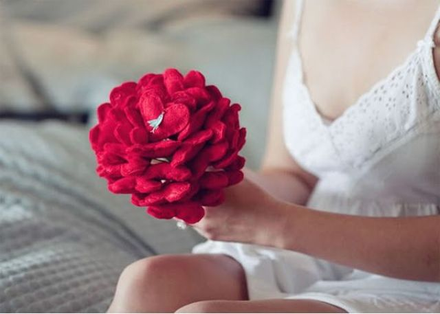 a non typical wedding bouquet composed of red felt hearts and with a littel bird is a chic and creative idea for a Valentine bride