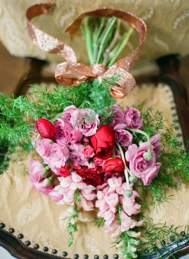 a bright Valentine wedding bouquet of pink, lavender and red blooms and greenery shows off all the traditional Valentine colors
