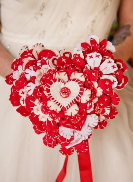 a bold red and white heart shaped Valentine wedding bouquet with a button on one of hearts is a lovely and bold idea to rock