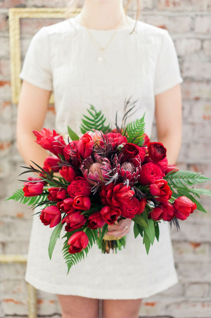 a gorgeous red and burgundy blooms and ferns and greenery is a beautiful statement with color for a Valentine bride