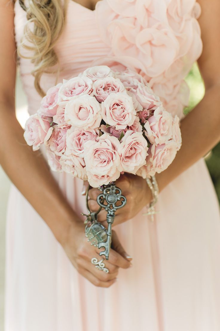 a lovely blush rose wedding bouquet with a wrap and vintage keys for detailing for a Valentine vintage bride