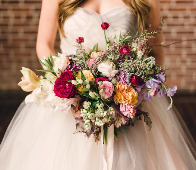 a bright and cool multi color wedding bouquet in lavender, blush, yellow, fuchsia and red, with whimsical leaves and greenery