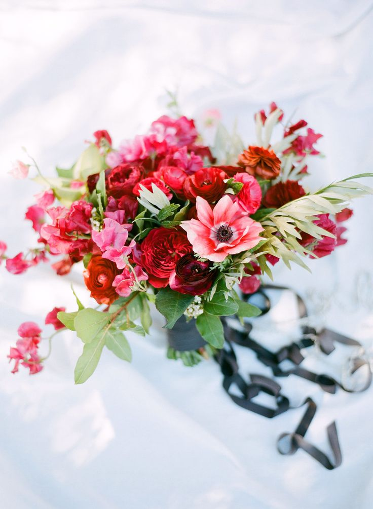 a pink, red, burgundy wedding bouquet with greenery is a bold and chic statement for a Valentine bride