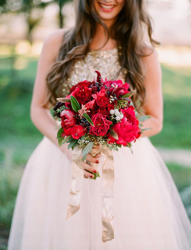 a super bold red and deep purple wedding bouquet with various berries, greenery and a gold glitter ribbon is romantic and stylish