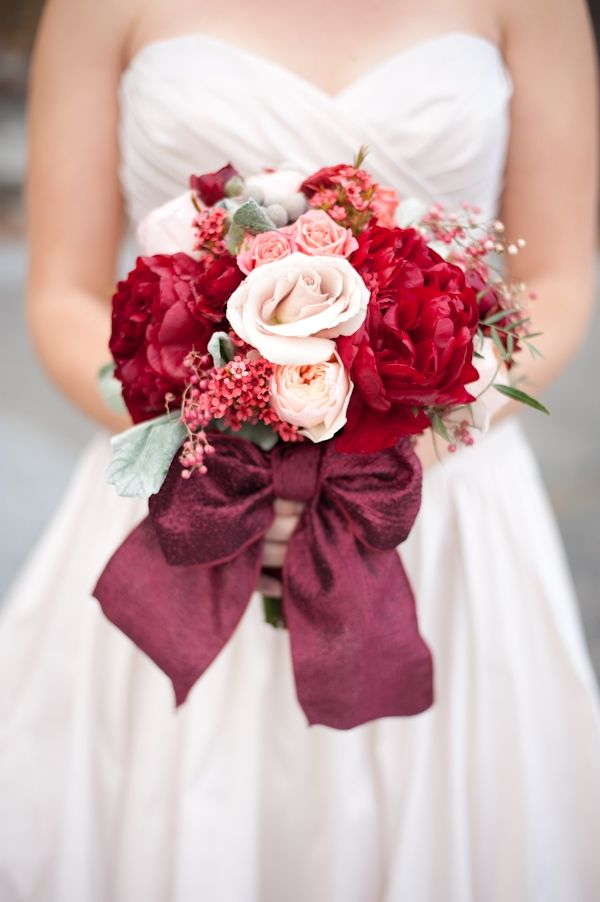 a bright wedding bouquet of blush, red, orange blooms, berries, cotton and a lovely burgundy ribbon bow is amazing for a Valentine wedding