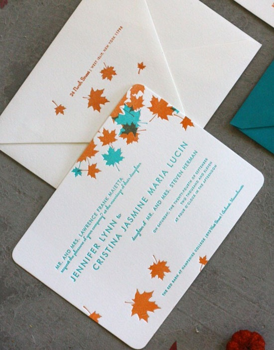 a colorful fall wedding invitation suite done with orange and aqua colored leaves