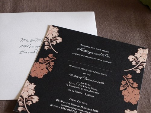 a black wedding invitation with gold and copper fall leaves printed on it for a chic and contrasting look